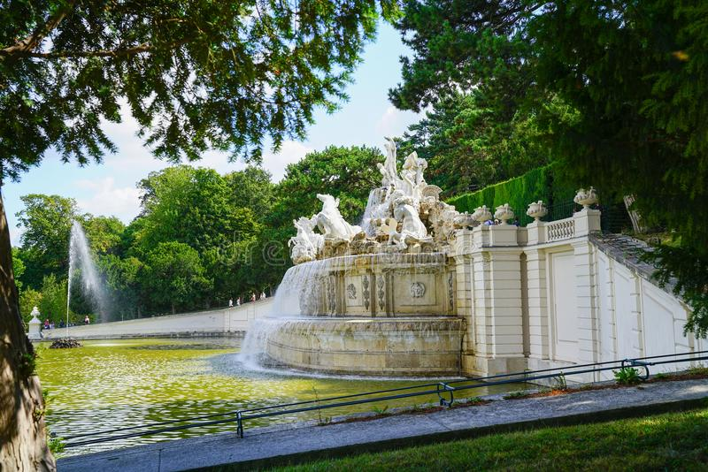 Tourists around large ornate Neptune Fountain and water feature. VIENNA,AUSTRIA - SEPTEMBER 4 2017; Tourists around large ornate Neptune Fountain and water stock images