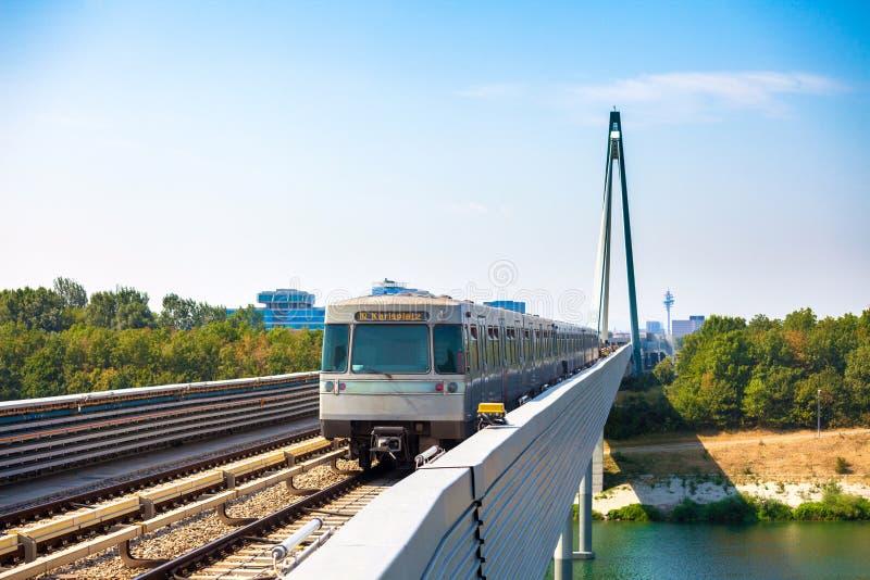 Vienna metro train passing a bridge over Danube river. VIENNA, AUSTRIA - AUGUST 6: Vienna metro train passing a bridge over Danube river, Austria royalty free stock image