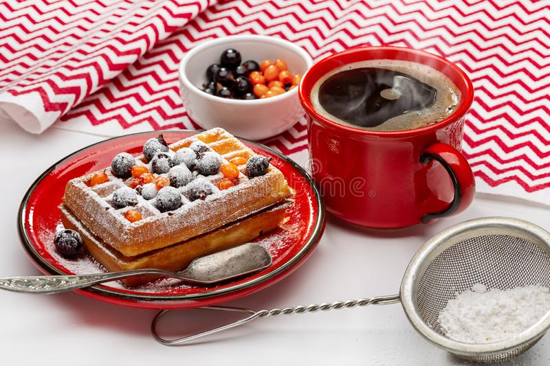 Viennese waffles sprinkled with powder and decorated with berries stock photos