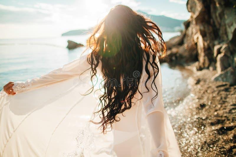 Viento en muchacha soñadora del pelo con el sunflare en la playa fotografía de archivo libre de regalías