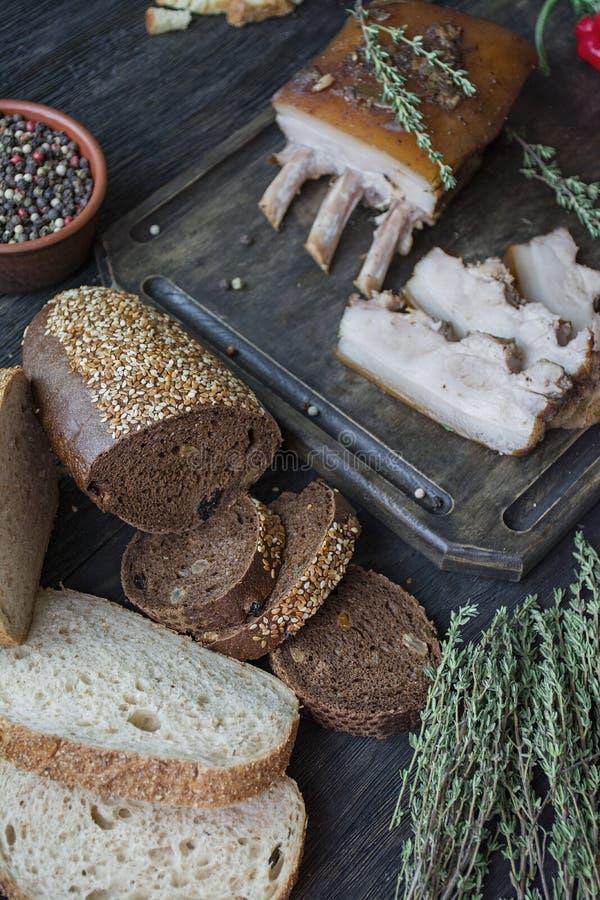 Vientre de cerdo cocido con las especias, tomillo, pimienta amarga, pan fresco Grasa ucraniana Plato tradicional de Ucrania De ma imagenes de archivo