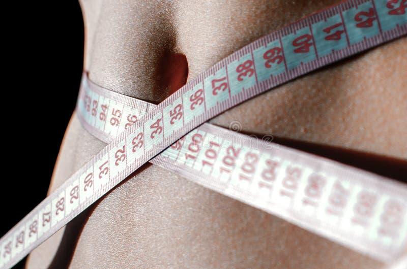 Vientre de la mujer con cinta métrica foto de archivo libre de regalías