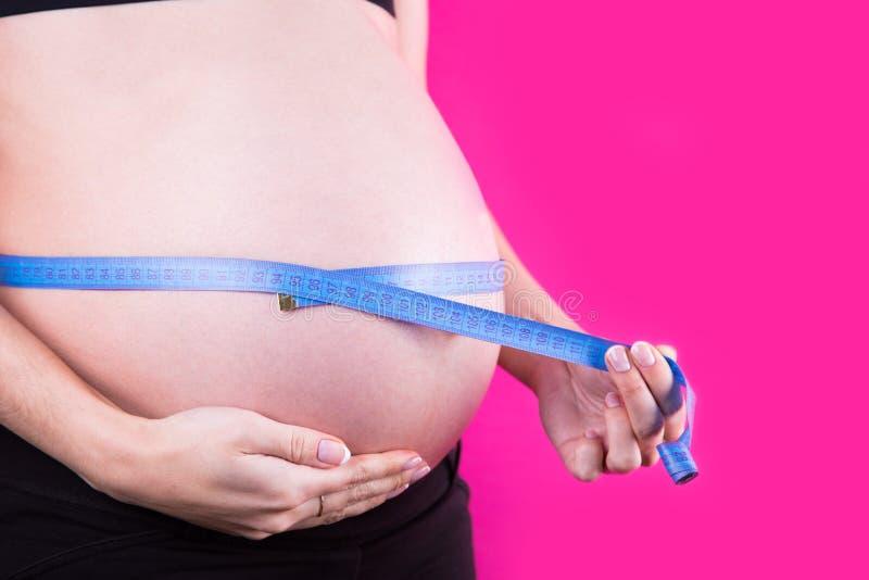 Vientre del primer de la mujer embarazada con cinta métrica atada alrededor en fondo rosado fotografía de archivo libre de regalías