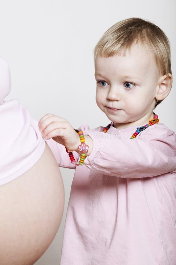 Vientre embarazado conmovedor de la niña imagen de archivo