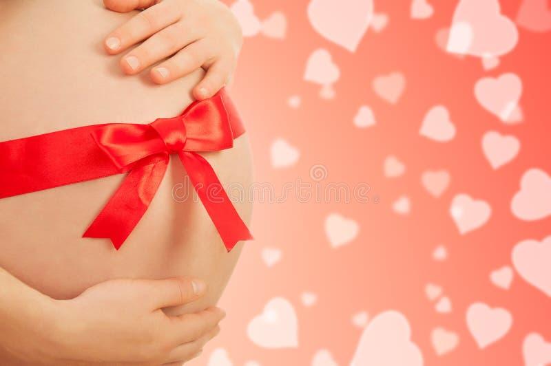 Vientre embarazado de la mujer con la cinta roja foto de archivo
