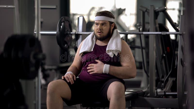 Vientre que frota ligeramente masculino gordo divertido, agotado después de entrenamiento, inseguridades foto de archivo