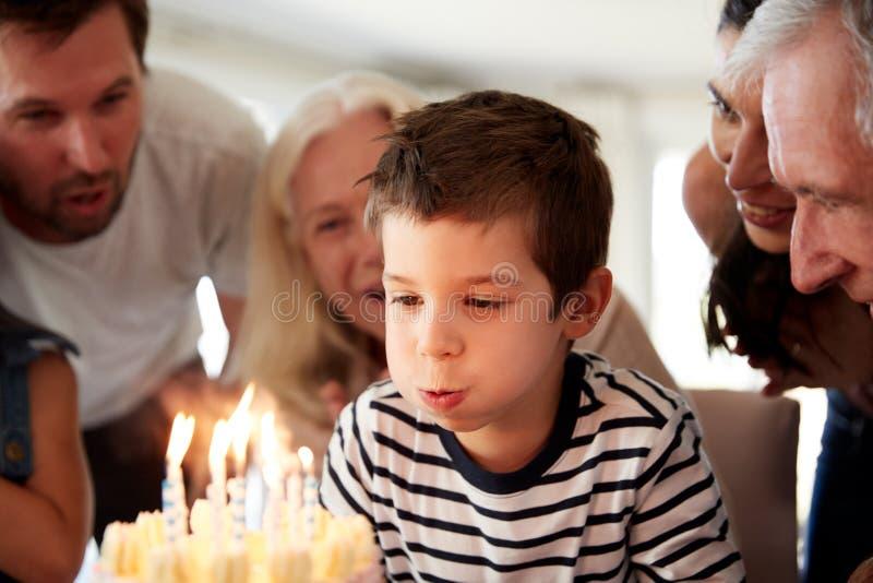 Vier éénjarigen het witte jongen vieren met familie die uit schouwt op zijn verjaardagscake, omhoog sluiten blazen royalty-vrije stock fotografie