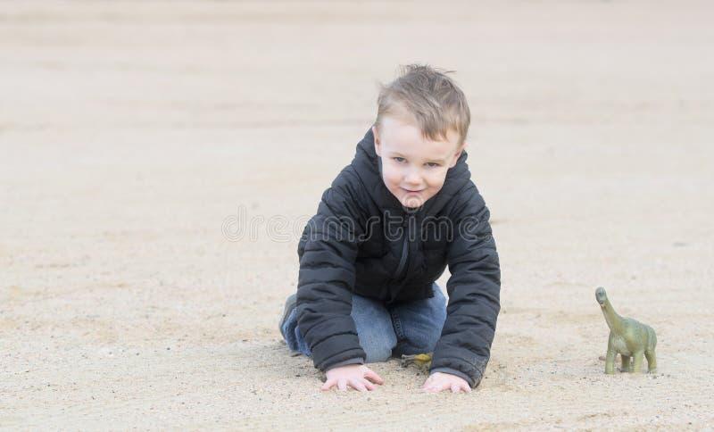 Vier Éénjarigen Jongen het Spelen op het Strand en het Zand met zijn Dinosaurussen in de Winterweer royalty-vrije stock foto