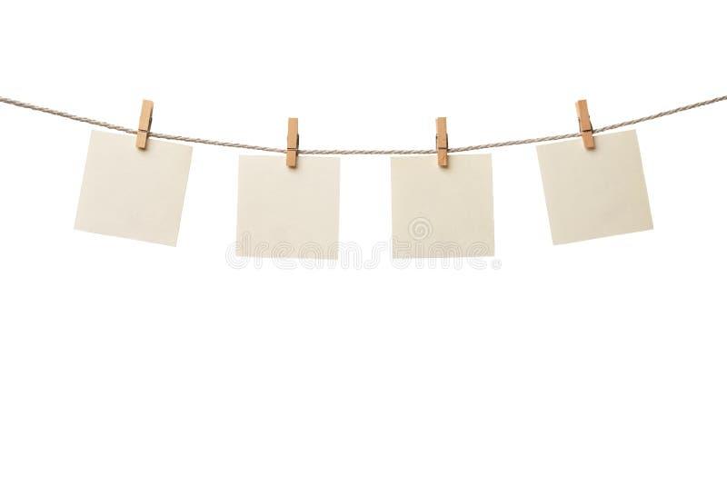 Vier alte leere Papieranmerkungen, die am Seil lokalisiert auf weißem Hintergrund hängen stockbild