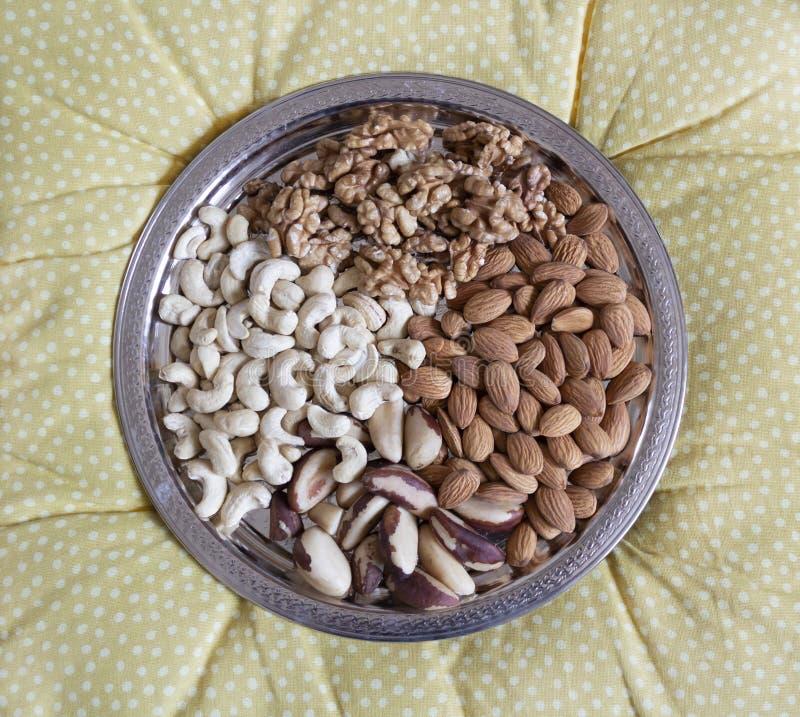 Vier Arten abgezogene Nüsse auf einem Silbertablett Walnüsse, Acajoubaum, Paranüsse, Mandeln lizenzfreie stockbilder