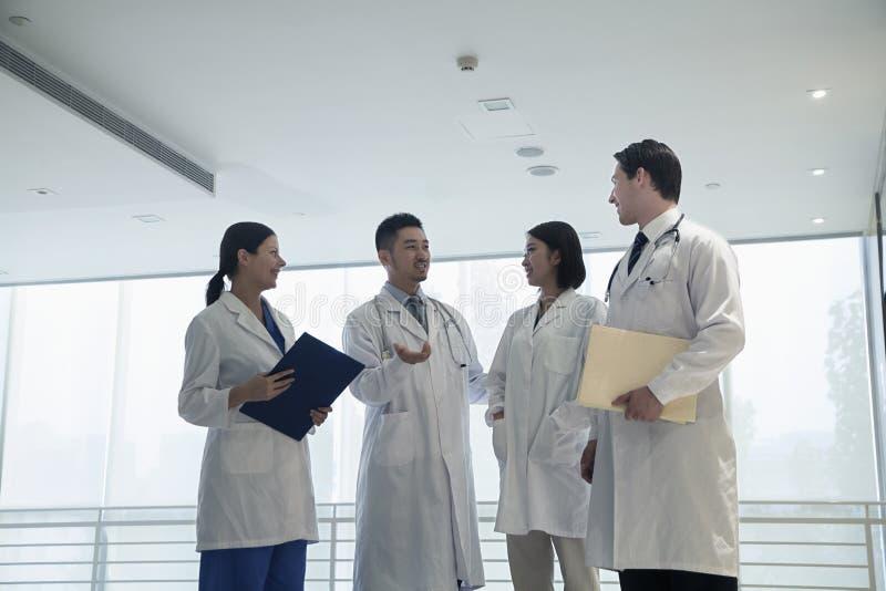 Vier artsen die, en in het ziekenhuis glimlachen bevinden zich spreken stock foto's