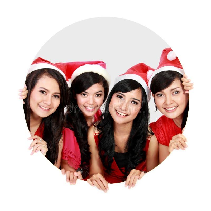 Vier asiatische Frauen mit Weihnachts-Sankt-Hut im Kreis stockfotografie