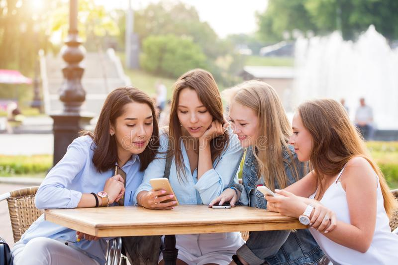 Vier attraktive junge Frauen benutzen Smartphones an einem Tisch im Park stockfotos