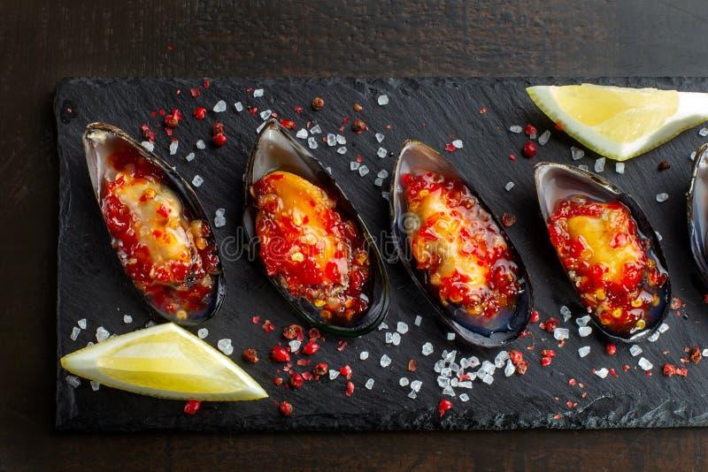 Vier Austern Frische Austern werden auf schwarzem Schiefer, grobes Salz wird besprüht herum ausgebreitet Meeresfrüchte stockfotos