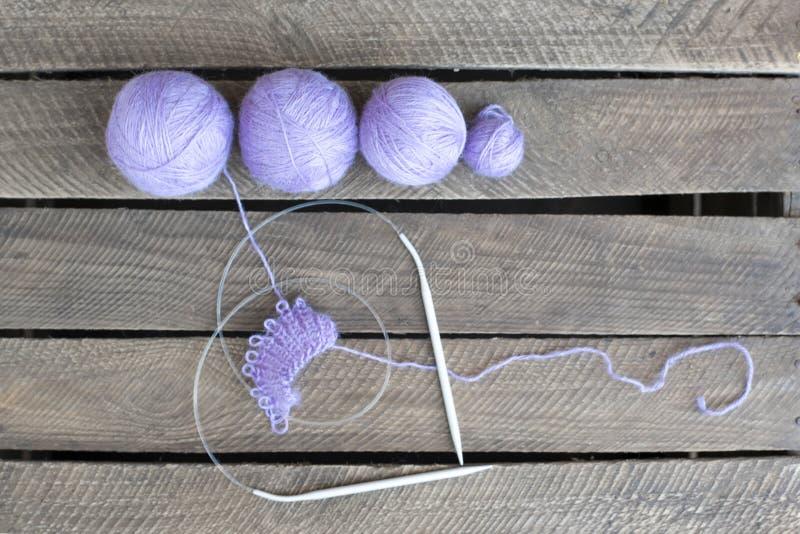 Vier Bälle lila Wolle und Nadel lizenzfreie stockbilder
