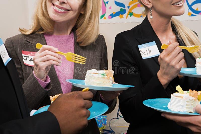 Vier Büroangestellte, die Kuchen essen lizenzfreie stockbilder