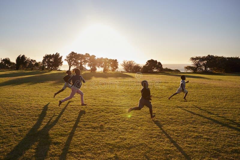 Vier basisschoolkinderen die op een open gebied lopen stock foto's