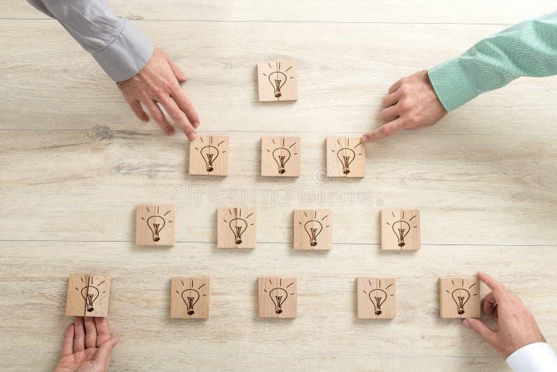 Vier bedrijfsmensen die houten blokken met gloeilampen plaatsen in a royalty-vrije stock foto