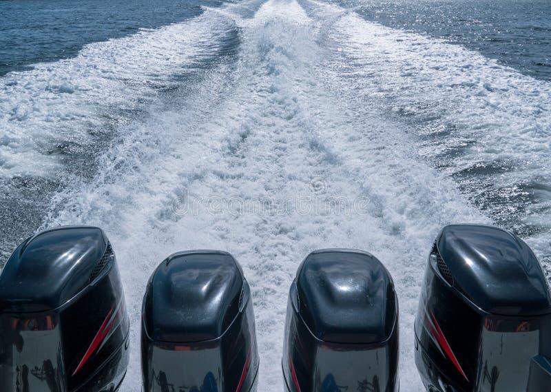 Vier Bootmotoren verlieten een pas van schuim op het water stock fotografie
