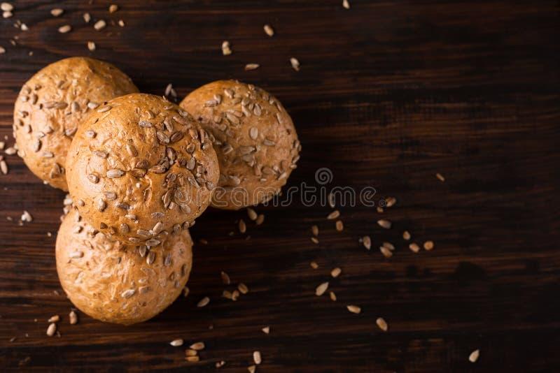 Vier Brötchen mit Samen auf einem dunklen hölzernen Hintergrund lizenzfreie stockfotografie