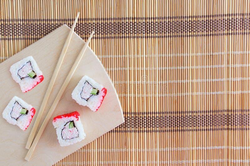 Vier broodjes met krabvlees en komkommer met vliegende vissenkuiten Op houten tribune met eetstokjes Foiedeken voor broodjes stock foto