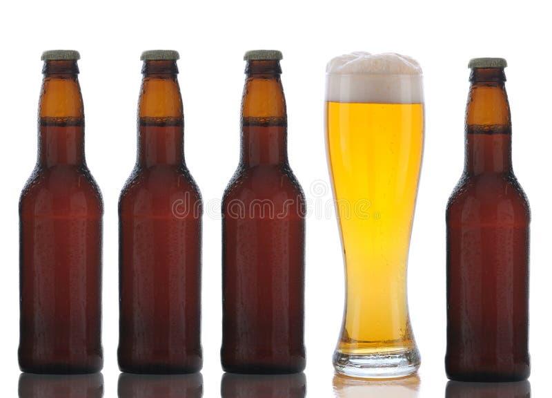 Vier Bruine Flessen van het Bier en Volledig Glas royalty-vrije stock foto