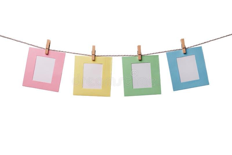 Vier bunte Papierfotorahmen, die am Seil lokalisiert auf Weiß hängen lizenzfreie stockfotografie