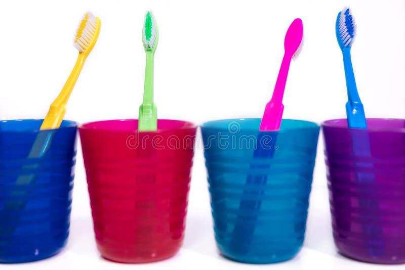 Vier bunte Schalen mit Zahnbürsten, weißer Hintergrund lizenzfreie stockfotos