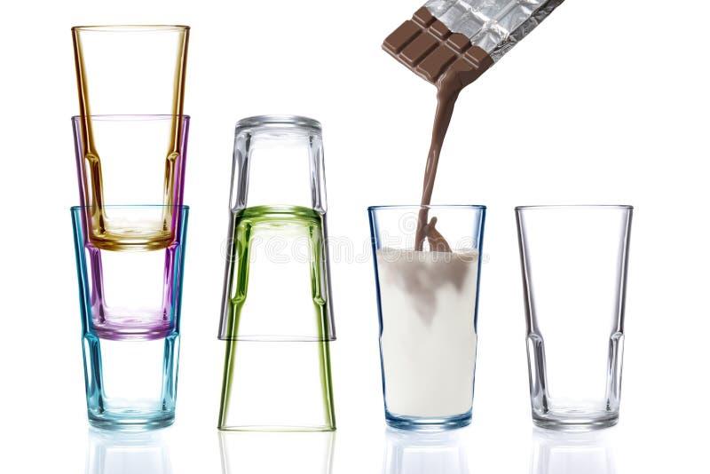 Vier bunte Trinkgläser, eins, das mit Kakao gefüllt wird stockbild