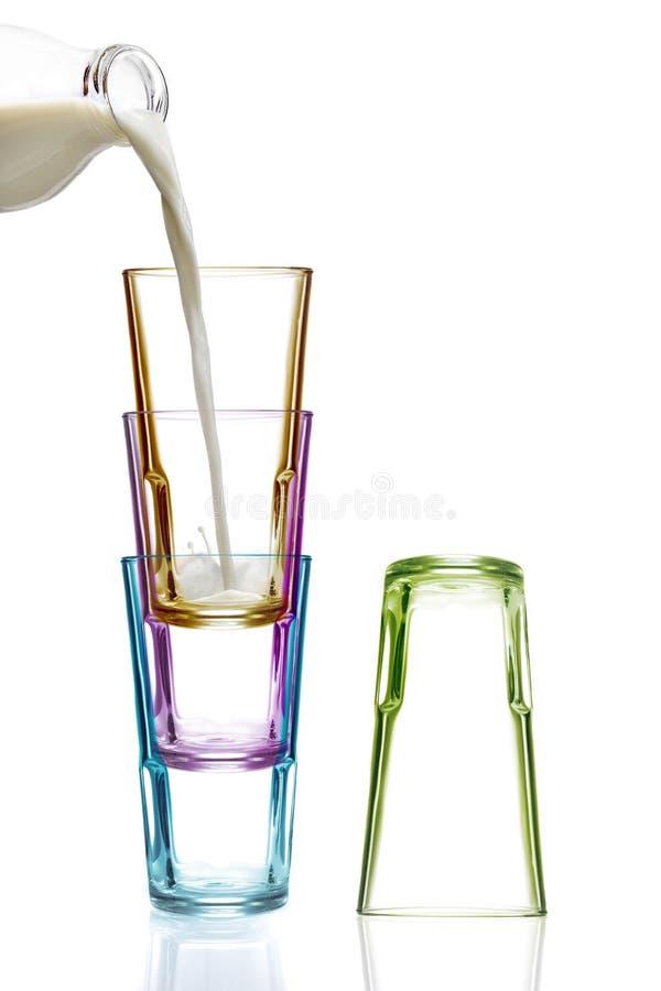 Vier bunte Trinkgläser, eins, das mit Milch gefüllt wird stockbilder