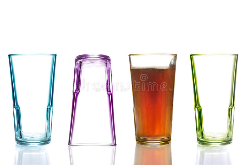 Vier bunte Trinkgläser, eins mit Kolabaum stockfotografie