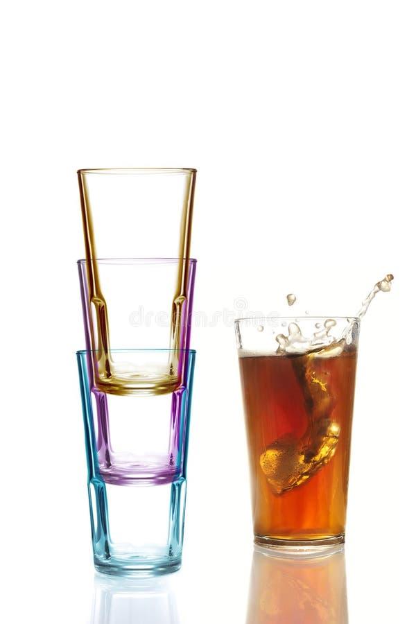 Vier bunte Trinkgläser, eins mit Kolabaum lizenzfreie stockbilder
