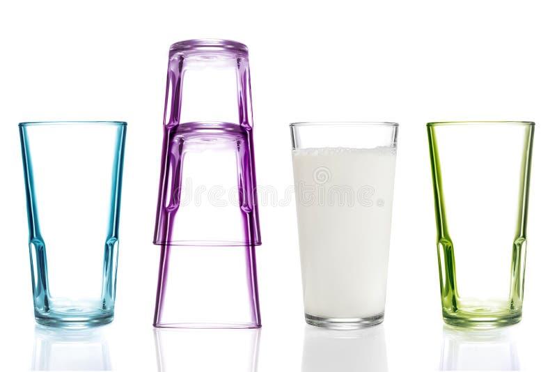 Vier bunte Trinkgläser, eins mit Milch lizenzfreies stockbild