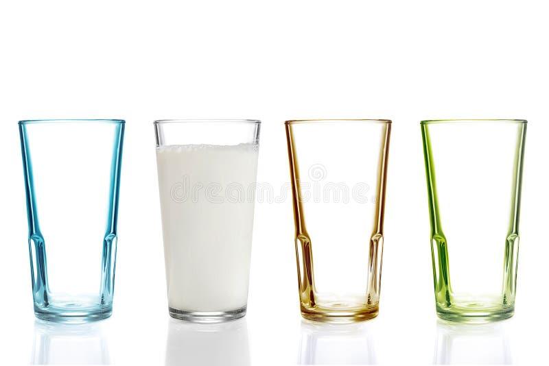 Vier bunte Trinkgläser, eins mit Milch lizenzfreie stockfotos