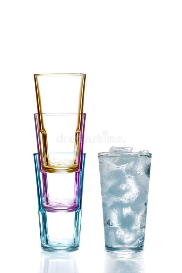 Vier bunte Trinkgläser, eins mit Wasser stockbild