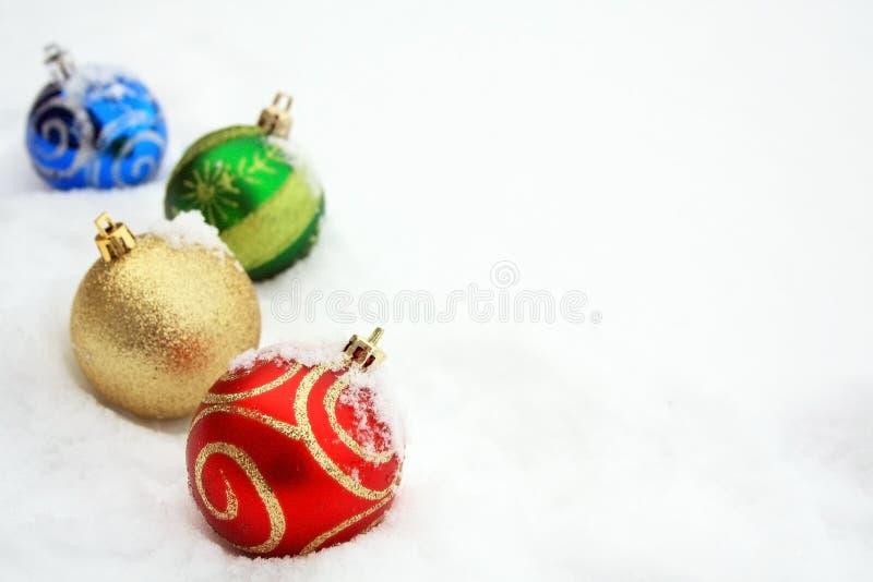 Vier bunte Weihnachtsbälle im Schnee stockfotografie