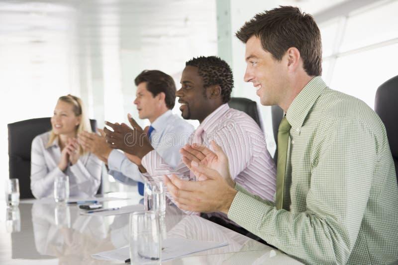 Vier businesspeople het toejuichen op vergadering stock afbeelding