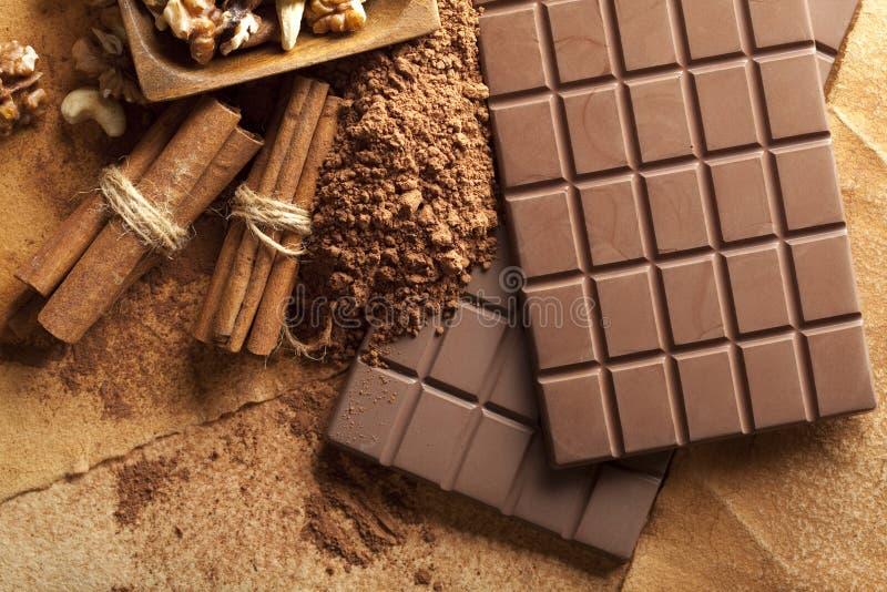 Vier chocoladerepen, pijpjes kaneel, cacao en gemengde noten stock foto