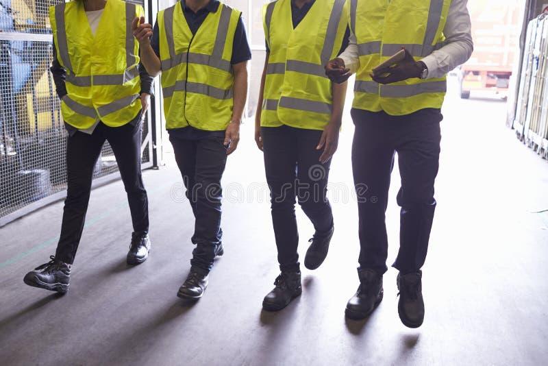 Vier collega's lopen in een industriële binnenlandse, lage sectie royalty-vrije stock foto's