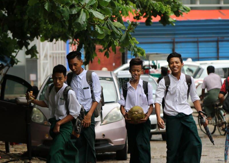 Vier collegians in Myanmarese eenvormig van universiteits wit overhemd en het groene Lange Yi-lopen die op de straat na schoolpro stock afbeelding