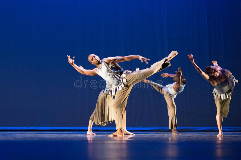 Vier dansers stellen tegen donkere achtergrond op stadium royalty-vrije stock afbeelding