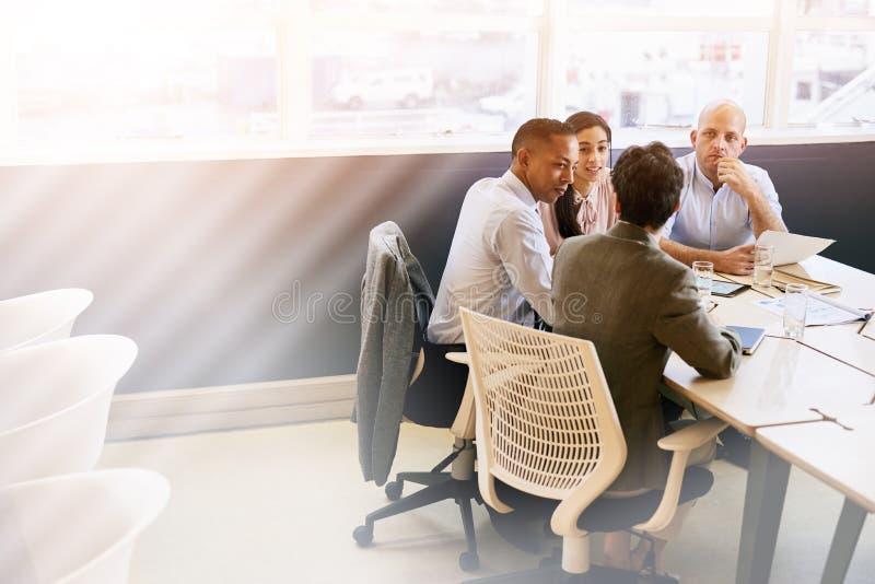 Vier eklektische Geschäftseinzelpersonen, die eine Sitzung im Konferenzsaal leiten stockfotografie