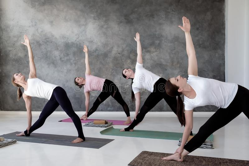 Vier Europese vrouwen die yoga, Trikonasana uitoefenen stellen royalty-vrije stock foto