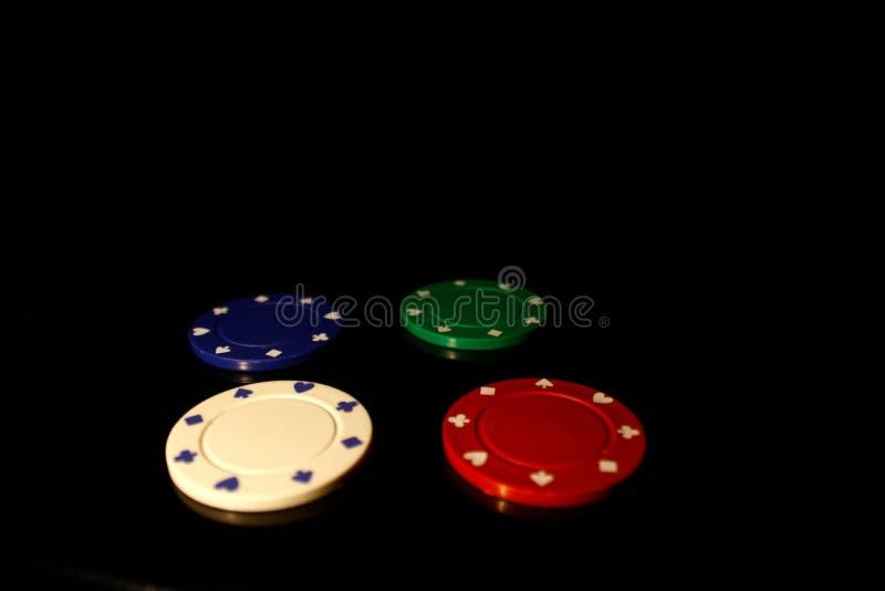 Vier Farben Casino-Chips schwarz mit Reflexion lizenzfreie stockbilder