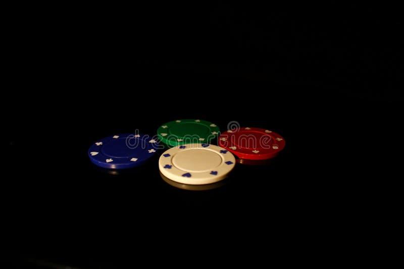 Vier Farben Casino-Chips schwarz mit Reflexion lizenzfreies stockbild