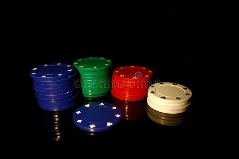 Vier Farben Casino-Chips Stapel mit blauem Chip vorne auf schwarz mit Reflektion stockbilder