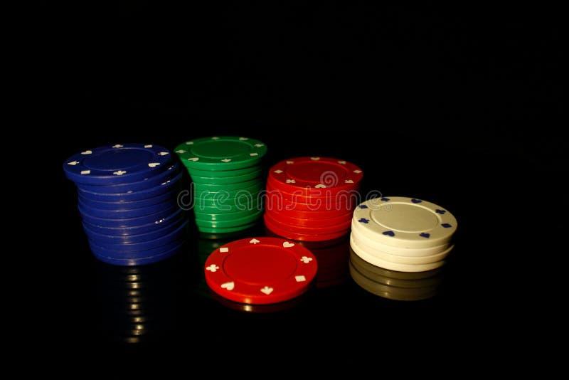 Vier Farben Casino-Chips Stapel mit rotem Chip vorne auf schwarz mit Reflektion stockfoto