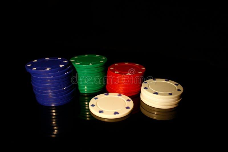Vier Farben Casino-Chips stapeln mit einem weißen Chip vorne auf schwarz mit Reflektion stockbilder