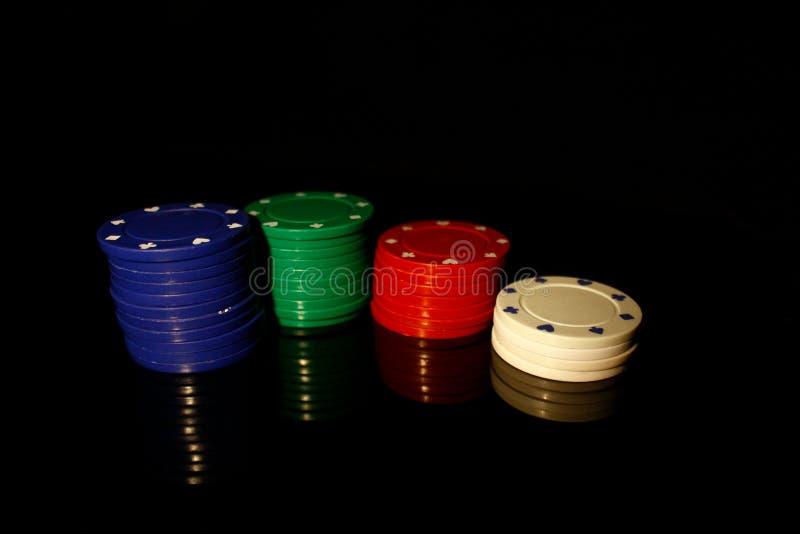 Vier Farben für Casino-Chips: blau, grün, rot weiß, schwarz mit Reflexion lizenzfreie stockfotografie
