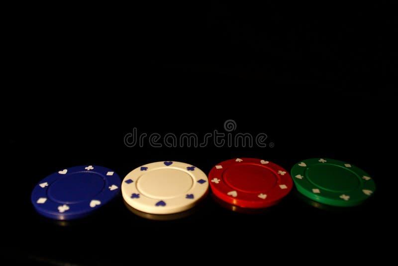 Vier farbige Casino-Chips, geradeaus auf schwarz angeordnet lizenzfreie stockbilder